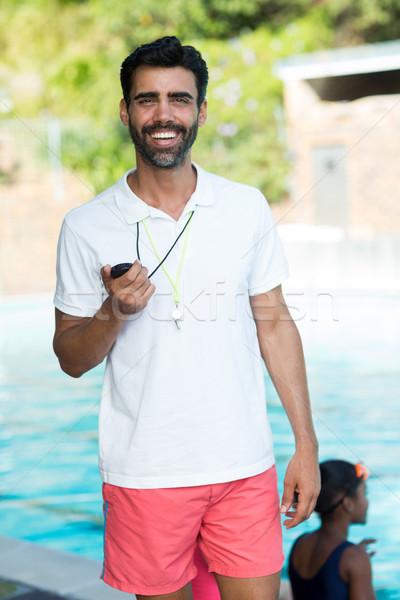 Male instructor standing at poolside Stock photo © wavebreak_media