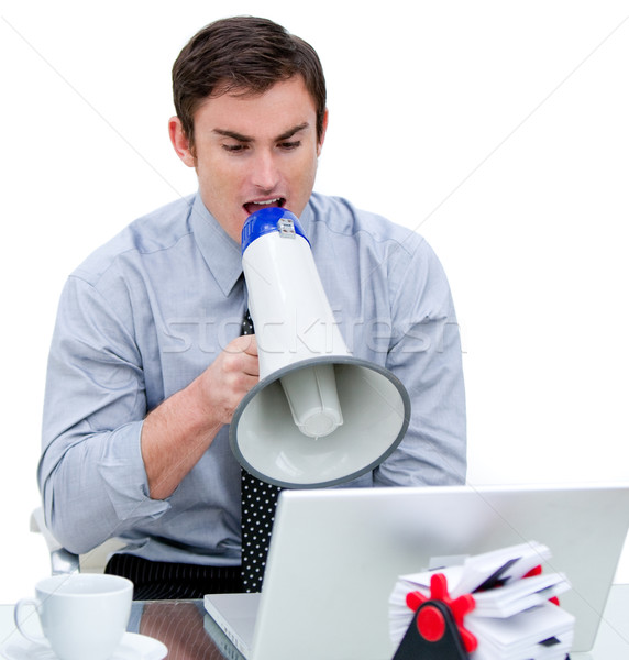 Angry businessman yelling through a megaphone sitting at his des Stock photo © wavebreak_media