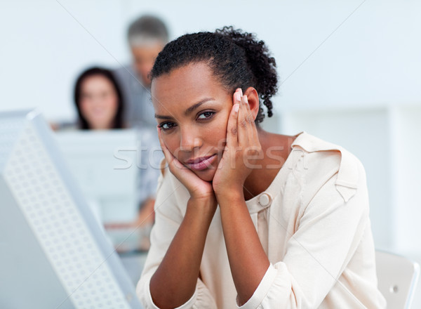 Stock photo: Bored young businesswoman at her desk