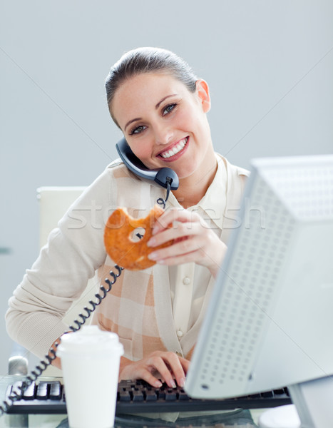 Self-assured businesswoman on phone eating a donnut Stock photo © wavebreak_media