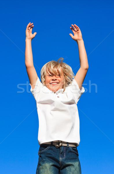 Fiatal gyerek ugrik levegő kék ég mosoly Stock fotó © wavebreak_media