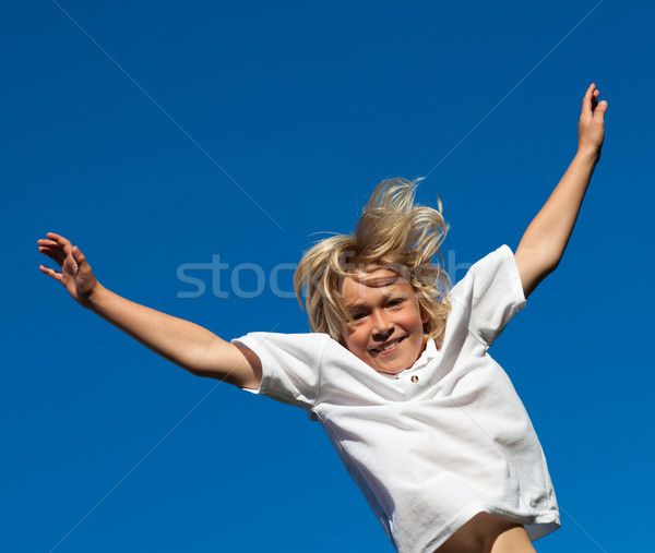 Smiling Kid Jumping in the air outdoor on a blue sky background Stock photo © wavebreak_media