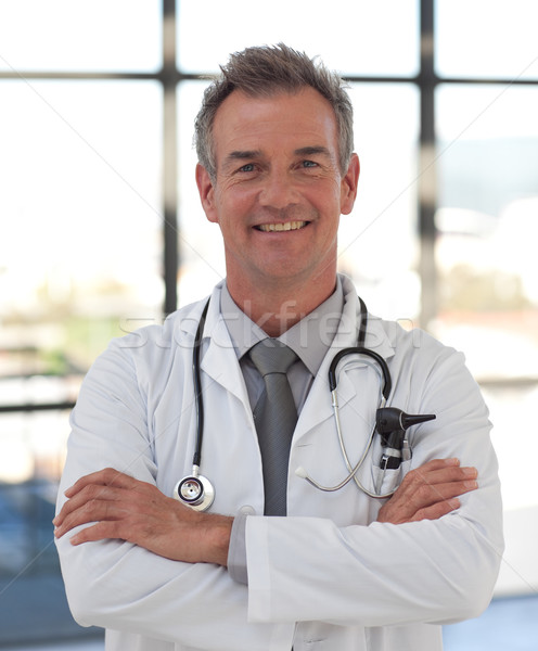Smiling doctor with folded arms looking at the camera   Stock photo © wavebreak_media