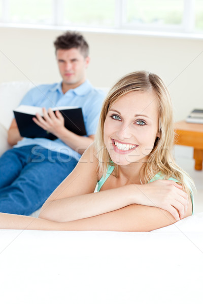 Girlfriend smiling at the camera while her boyfriend is reading a book on the sofa Stock photo © wavebreak_media
