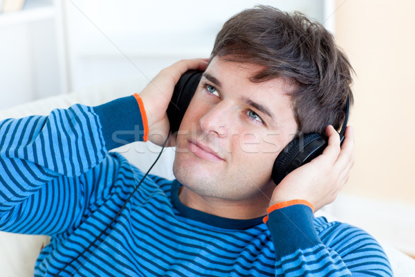 привлекательный молодым человеком прослушивании музыку сидят Жилье Сток-фото © wavebreak_media