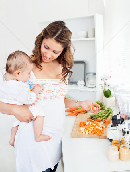 Stock photo: Young mother holding her baby while  preparing carrot for lunch in the kitchen