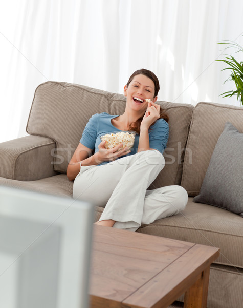 Cheerful woman watching television and eating pop corn in the living-room Stock photo © wavebreak_media