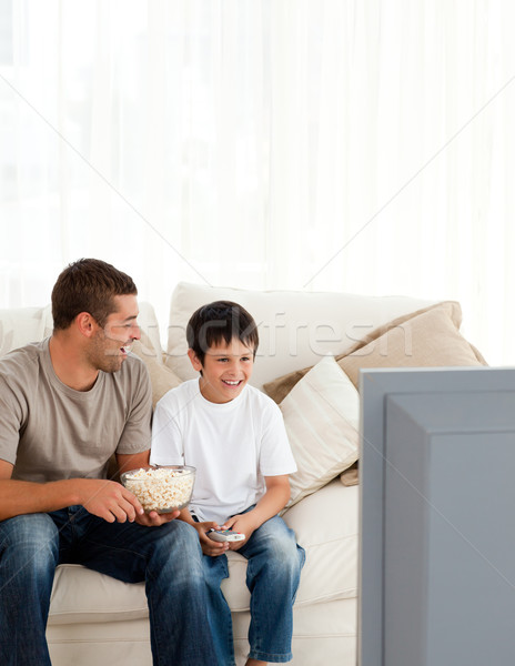Happy boy watching television with his father on the sofa at home Stock photo © wavebreak_media
