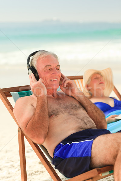 Man listening to music while his wife is sleeping Stock photo © wavebreak_media