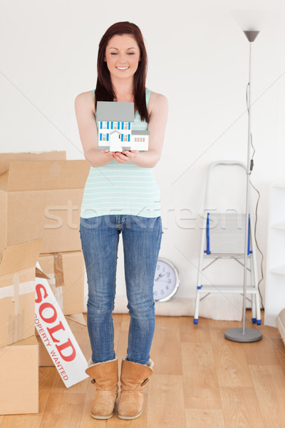 Beautiful red-haired woman holding a miniature house standing on the floor at home Stock photo © wavebreak_media