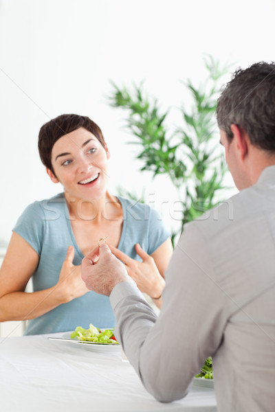 Stock photo: Man proposing to his excited girlfriend during dinner in a restaurant