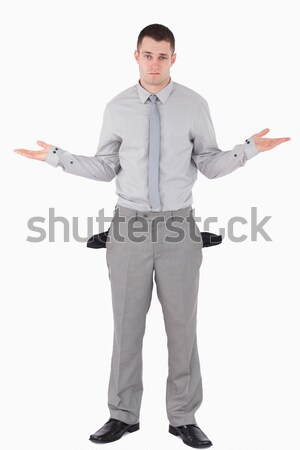 Portrait of a young businessman with empty pockets against a white background Stock photo © wavebreak_media