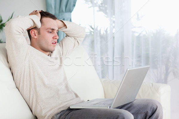 Sad man working with his notebook in his living room Stock photo © wavebreak_media