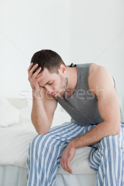 Stock photo: Portrait of an exhausted man sitting on his bed while looking away from the camera