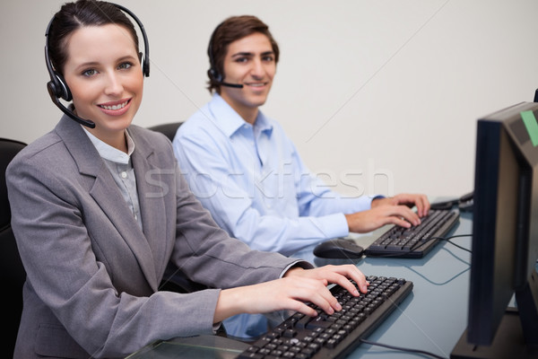 Side view of smiling young call center agents at work Stock photo © wavebreak_media