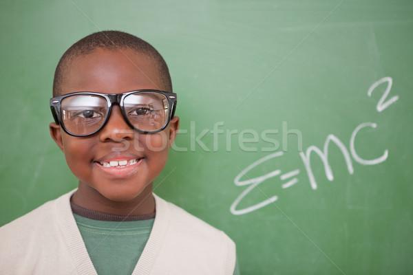 Schoolboy posing with the the mass-energy equivalence formula on a blackboard Stock photo © wavebreak_media