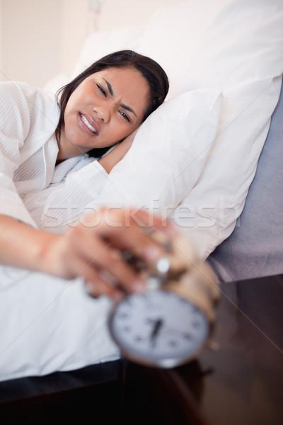 Fiatal nő fájdalom fülek ébresztőóra ágy hálószoba Stock fotó © wavebreak_media