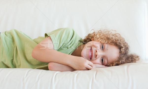 Happy boy lying on a sofa while looking at the camera Stock photo © wavebreak_media