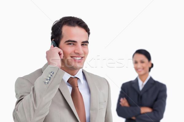 笑みを浮かべて セールスマン 携帯電話 同僚 後ろ 白 ストックフォト © wavebreak_media