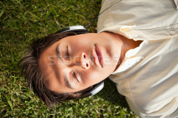 Man with his eyes closed as he uses headphones to listen to music while he lies down on the grass Stock photo © wavebreak_media