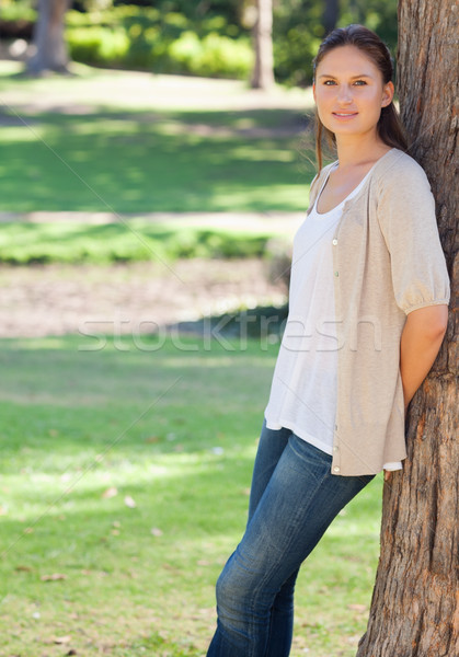 Woman in the park leaning against a tree Stock photo © wavebreak_media