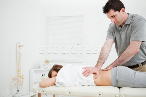 Serious practitioner massaging the lower back of a woman in a room Stock photo © wavebreak_media