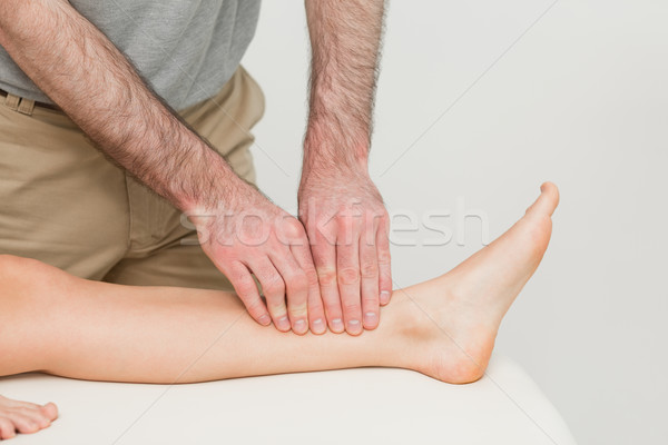 Doctor using his fingertips to massage a calf in a room Stock photo © wavebreak_media