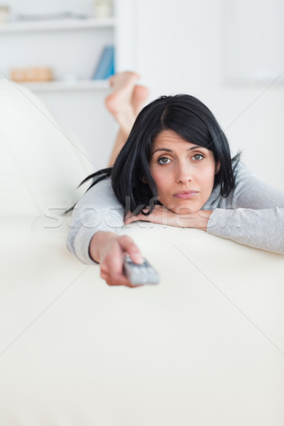 Woman pressing on a television remote while laying on a sofa in a living room Stock photo © wavebreak_media