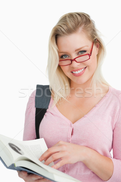 Happy young woman wearing glasses while holding a novel against a white background Stock photo © wavebreak_media