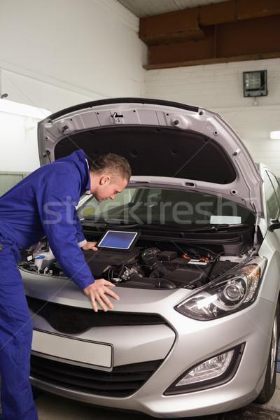 Concentrado mecânico olhando carro motor garagem Foto stock © wavebreak_media