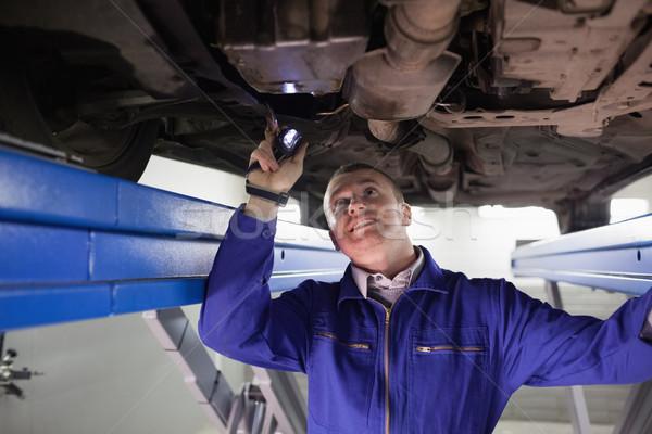 Smiling mechanic illuminating a car with a flashlight in a garage Stock photo © wavebreak_media