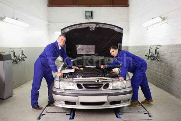 Mechanics leaning on a car looking at camera in a garage Stock photo © wavebreak_media