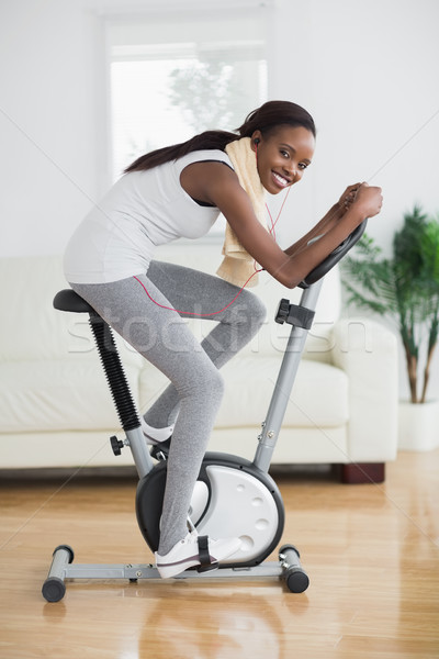 Side view of a concentrated black woman doing sport in a living room Stock photo © wavebreak_media