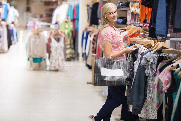 Woman standing in a shop holding bags smiling  Stock photo © wavebreak_media