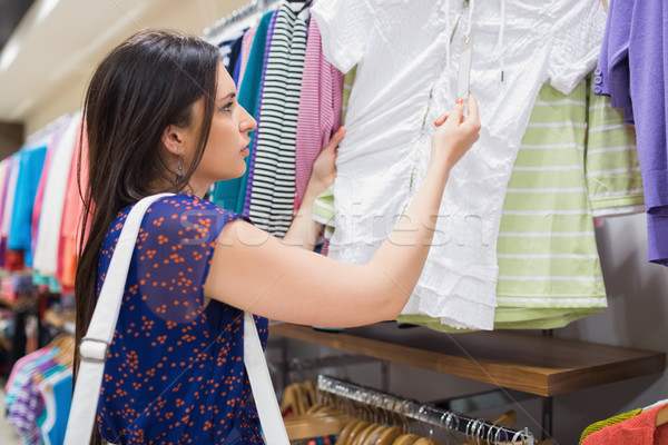 Woman looking at price tag of clothes at the shopping mall Stock photo © wavebreak_media
