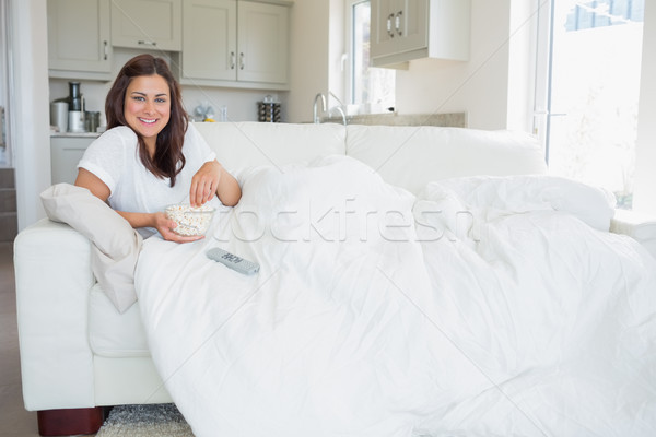 Brunette watching television while eating popcorn in the living room Stock photo © wavebreak_media