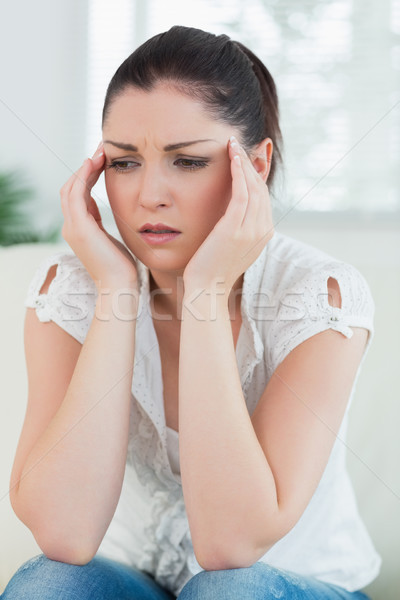 Stressed woman sitting on the couch in a living room and holding hands against head Stock photo © wavebreak_media