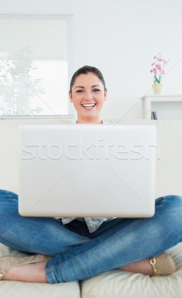 Stock photo: Laughing woman sitting cross-legged on a couch in a living room and using a laptop