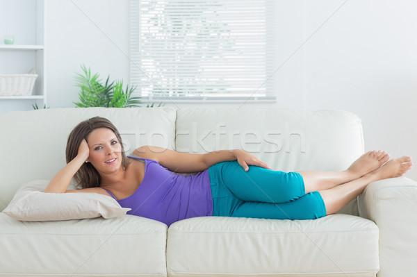 Happy brunette lying on sofa in the living room Stock photo © wavebreak_media
