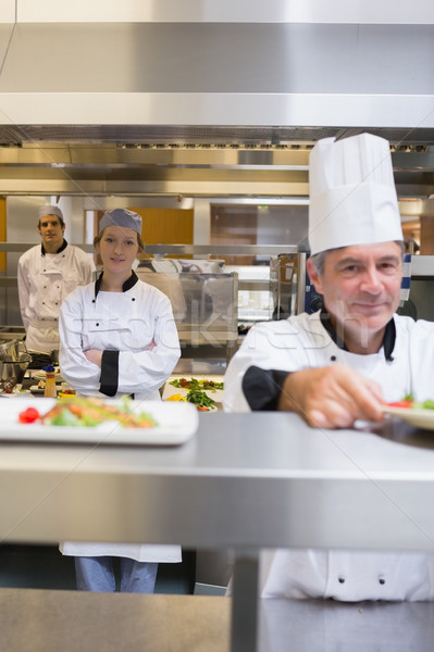 Restaurant kitchen with Chef's standing at different stations Stock photo © wavebreak_media
