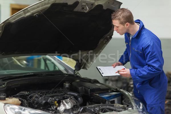 Mechanic with clipboard examining car engine Stock photo © wavebreak_media