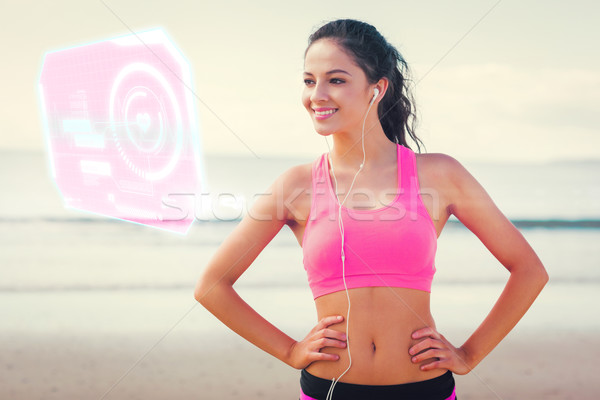 Stock photo: Composite image of beautiful smiling healthy with earphones on b