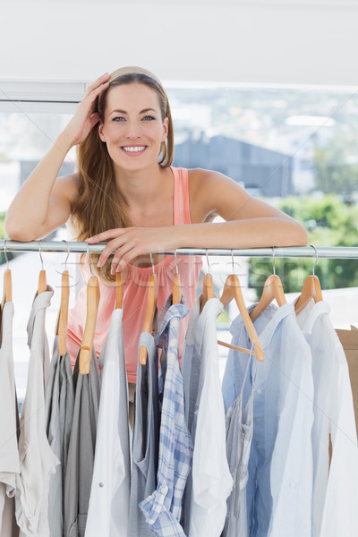 Beautiful female fashion designer with rack of clothes in store Stock photo © wavebreak_media