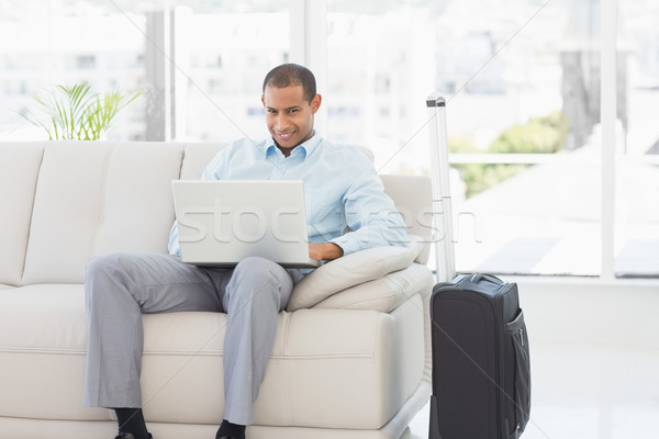 Happy businessman using laptop waiting to depart on business tri Stock photo © wavebreak_media