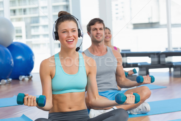 Fit people listening to music while lifting dumbbell weights Stock photo © wavebreak_media
