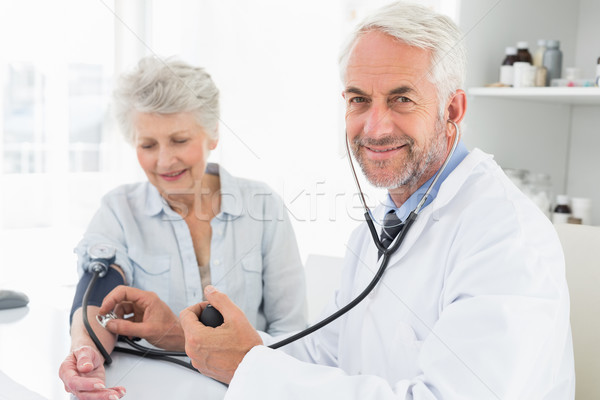 Doctor taking the blood pressure of his retired patient Stock photo © wavebreak_media