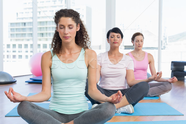 Women in lotus pose with eyes closed at fitness studio Stock photo © wavebreak_media