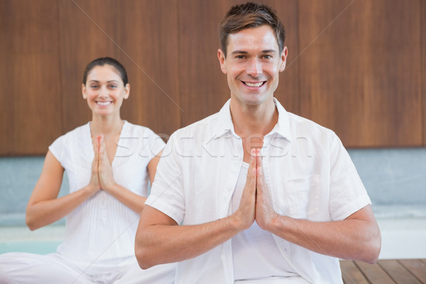 Peaceful couple in white sitting in lotus pose together Stock photo © wavebreak_media