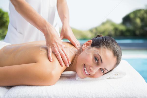 Happy brunette getting a massage poolside Stock photo © wavebreak_media