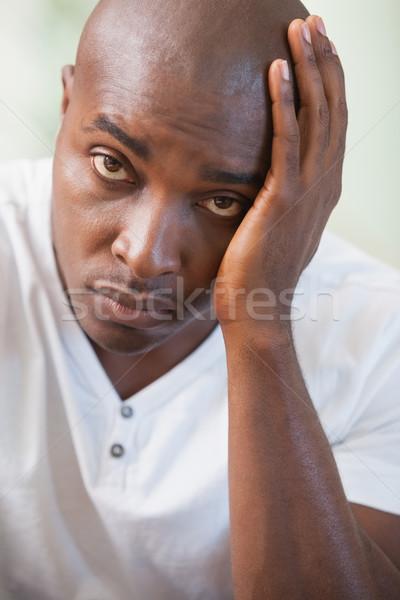 Zaklatott férfi ül kanapé néz kamera Stock fotó © wavebreak_media
